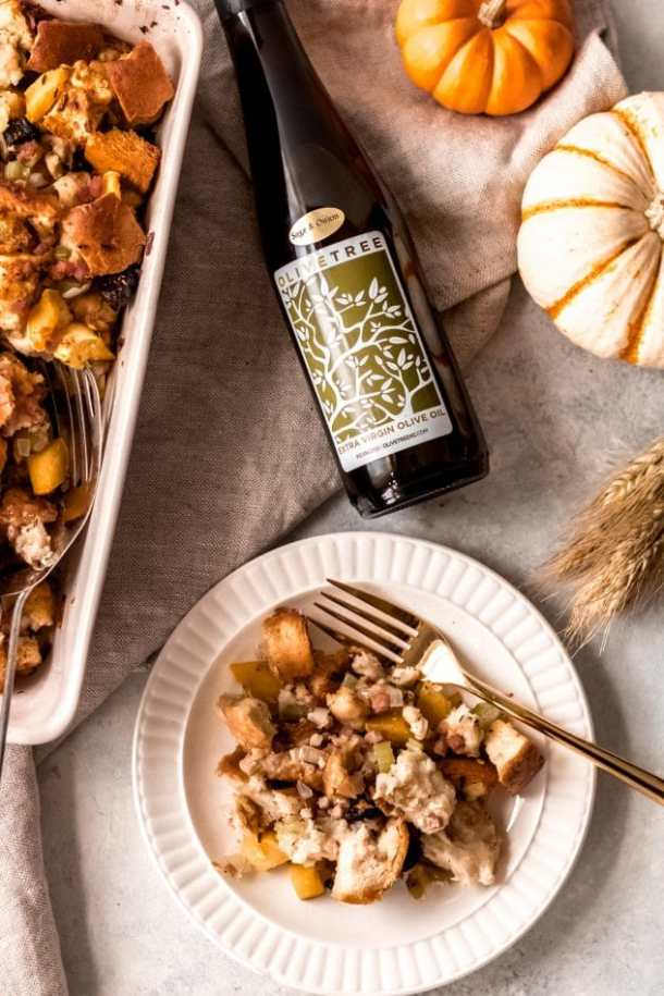 a 9x13 dish of sage, fig, and pancetta stuffing on a table with plates and forks and a serving spoon and a bottle of sage and onion olive oil from Olive Tree.