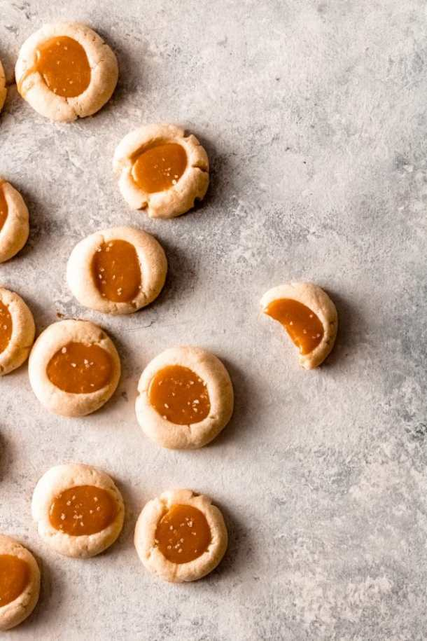 several salted caramel thumbprint cookies gathered on the left side of the image with the cookie with furthest to the right having a bite out of it