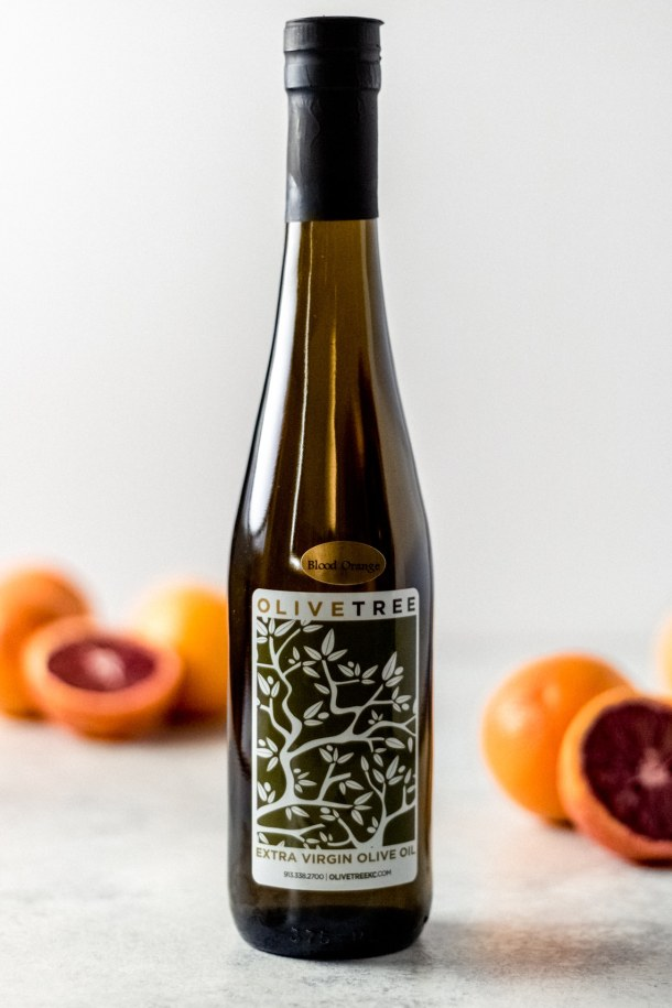 a bottle of Olive Tree's blood orange olive oil. There are blood oranges in the background