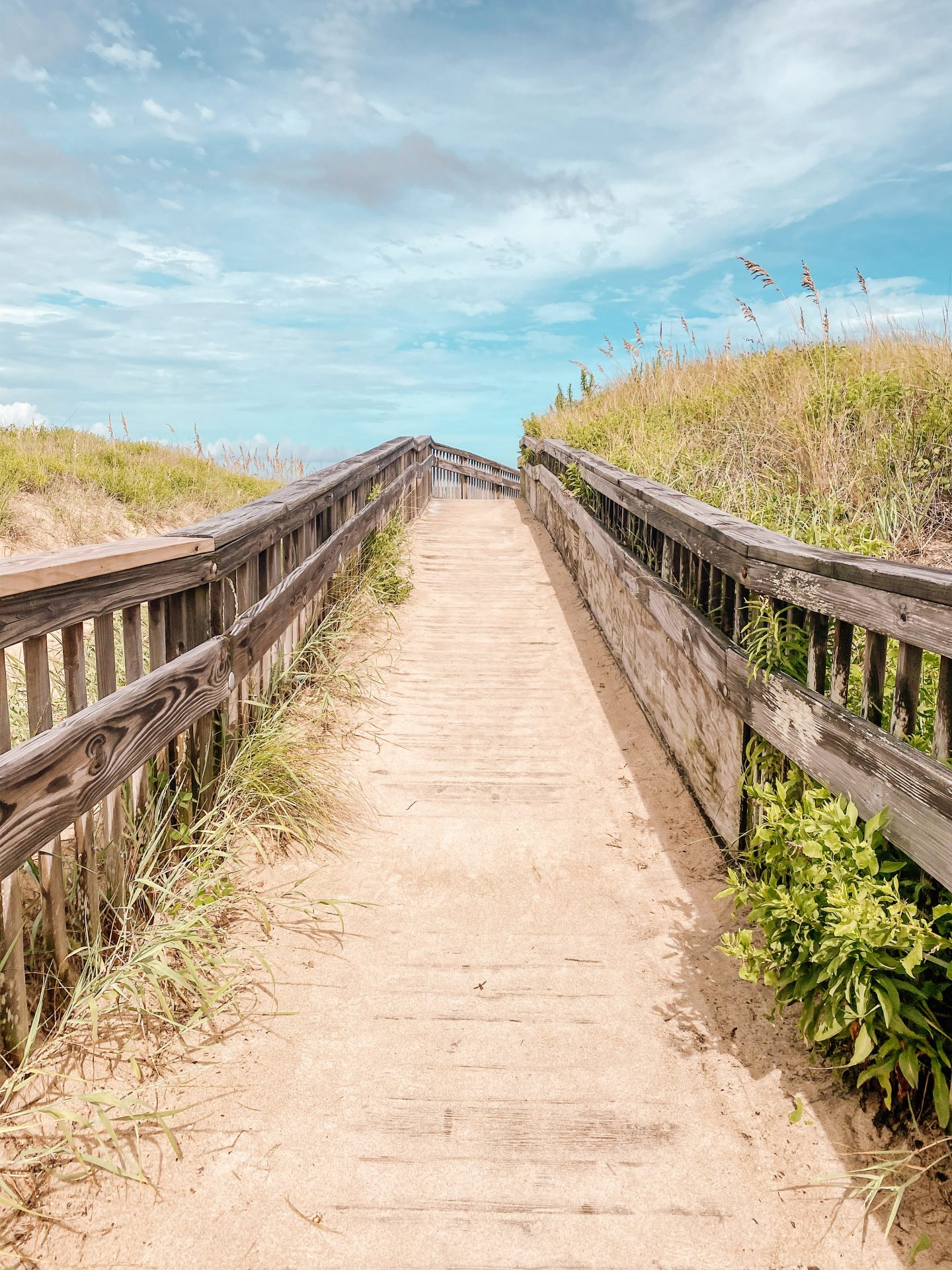 Blue skies with fluffy clouds overlooking a wooden walkway leading to the ocean in the outer banks of North Carolina while on a road trip
