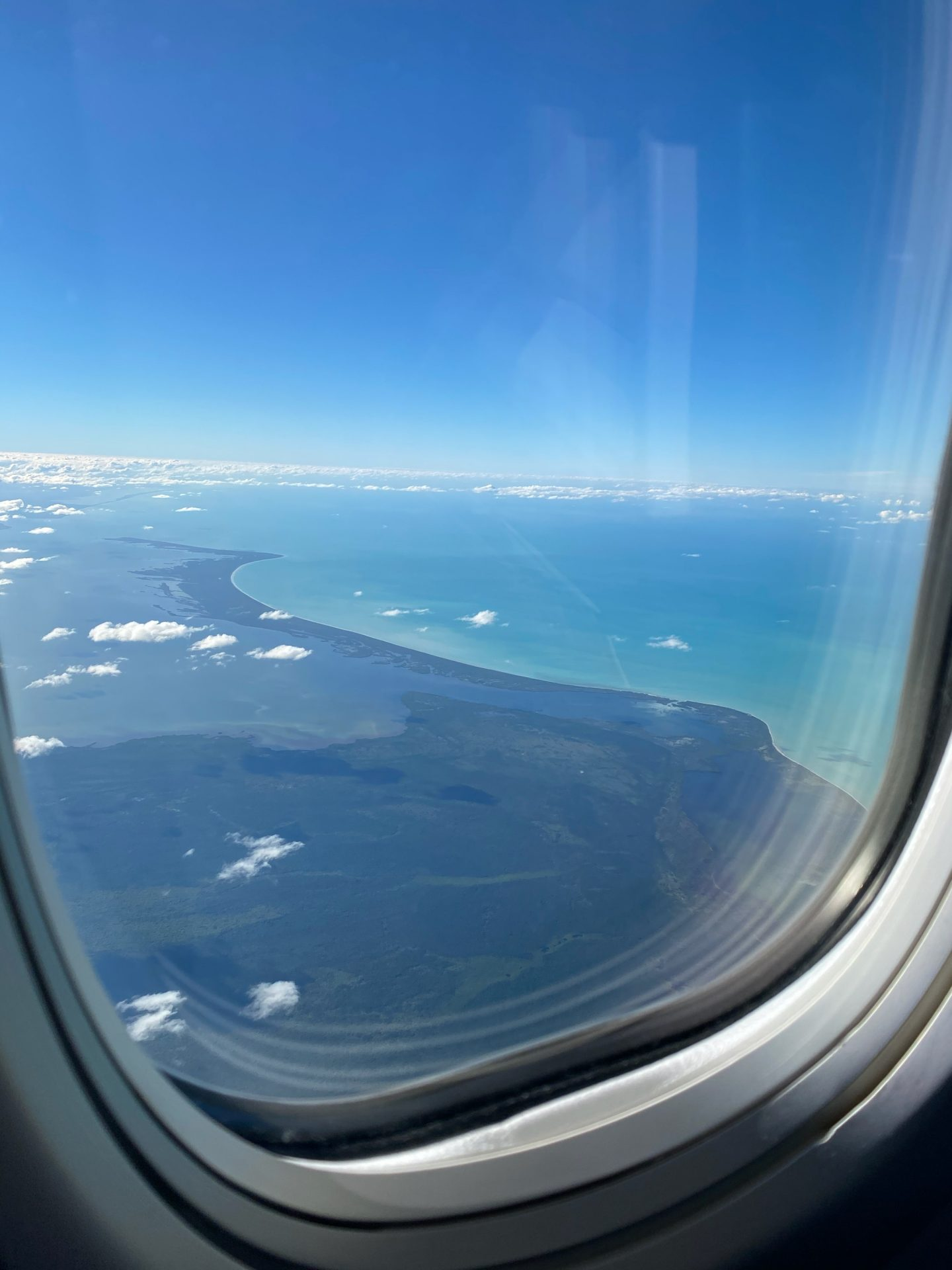 Looking out of a plane window to see clouds and a tropical blue ocean