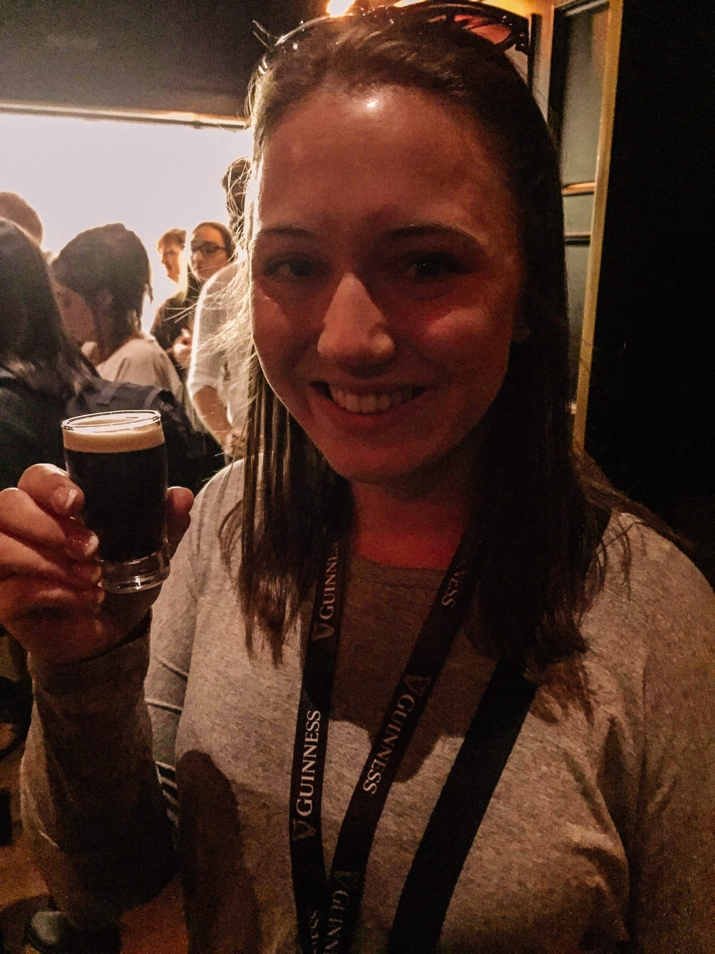 Woman traveling to Dublin Ireland at Guinness Storehouse holding up a small glass of beer smiling.