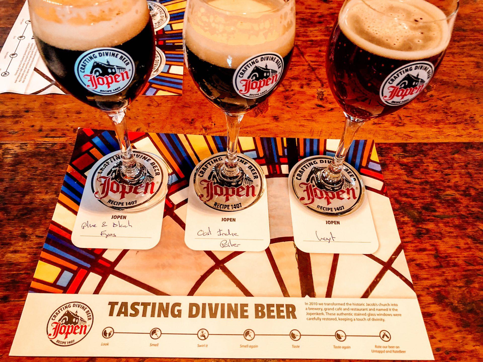 European Beer Travel Jopen Tasting Divine Beer three glasses of dark beer sitting on a card describing them.