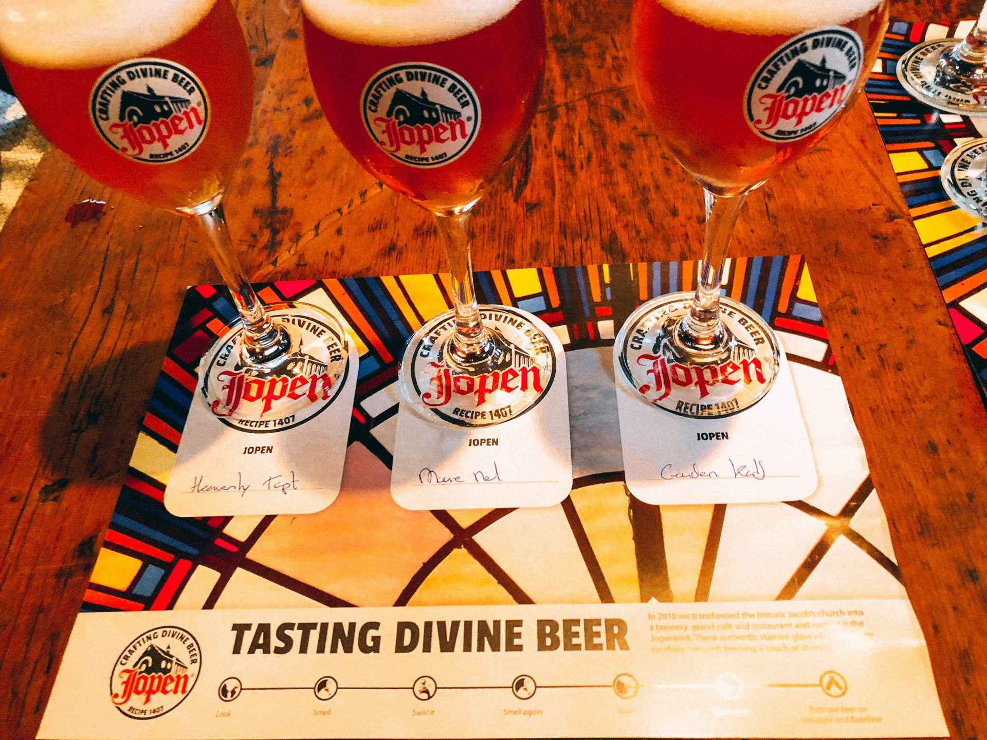 European Beer Travel Jopen Tasting Divine Beer three glasses of golden beer sitting on a card describing them.