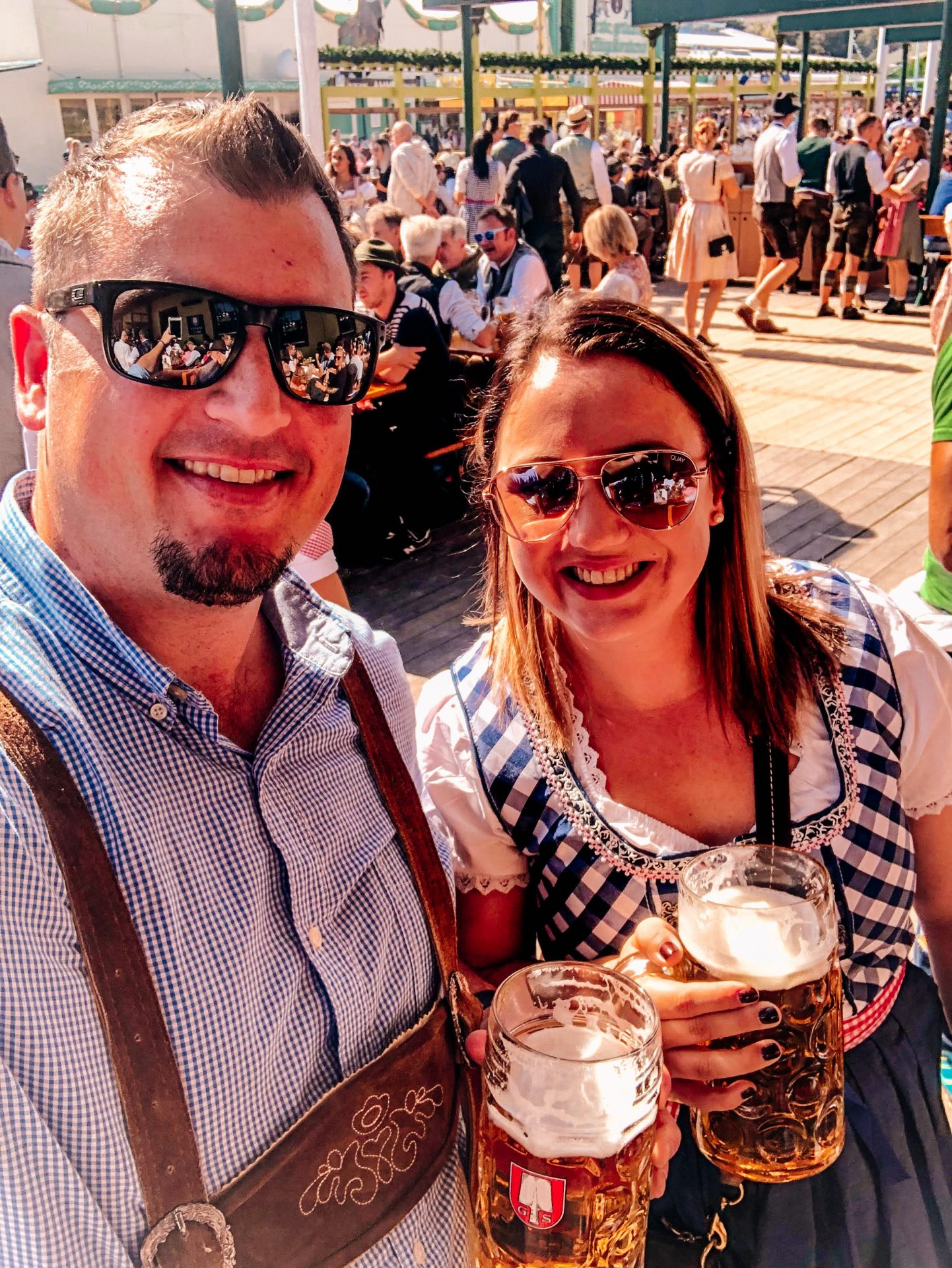 Man and Woman wearing traditional German clothing lederhosen & a dirndl, sunglasses, standing next to each other smiling holding 1L mugs of beer at Oktoberfest in Munich Germany Europe
