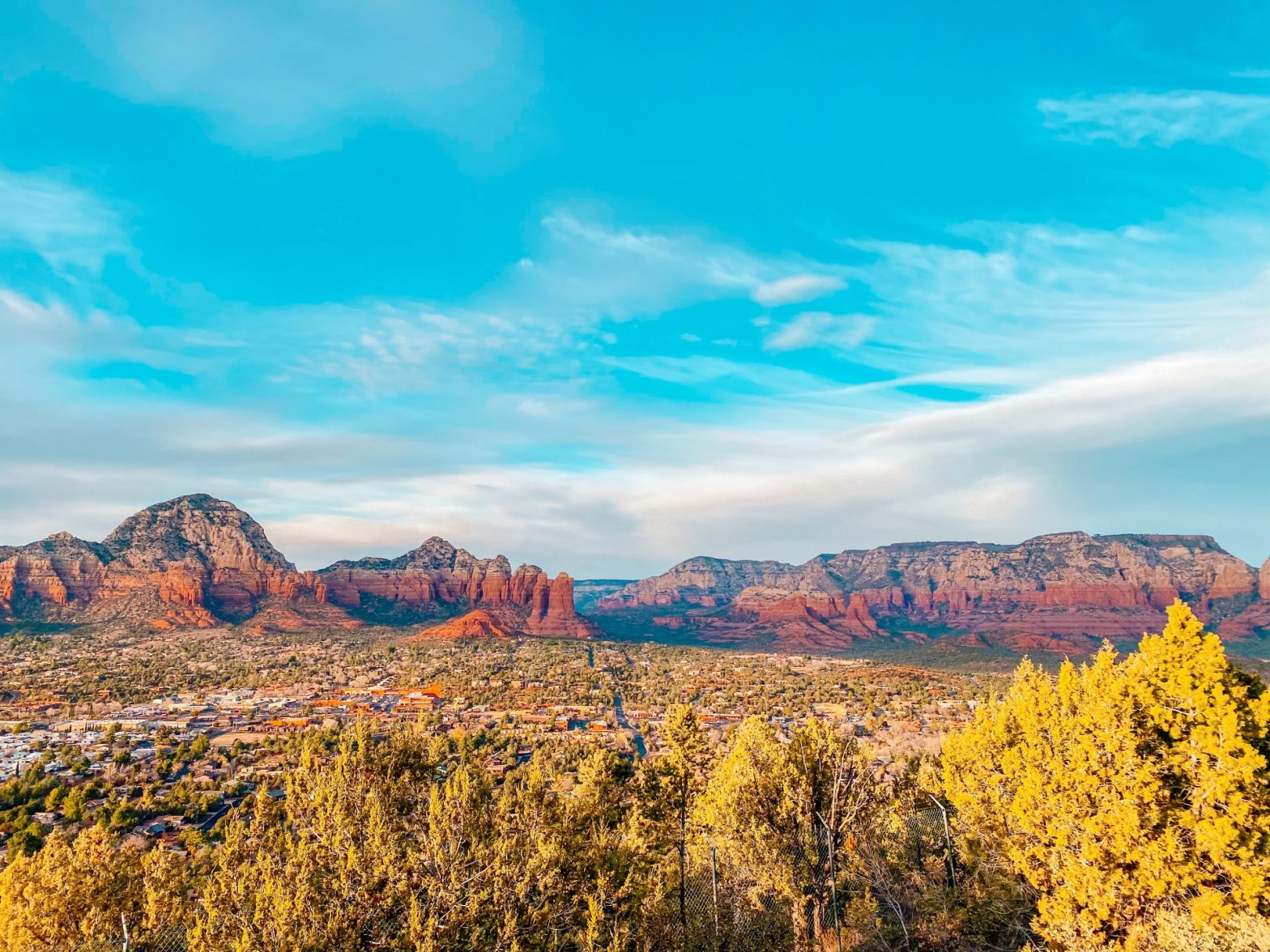 View out over the city of Sedona Arizona seeing the downtown area below and red rock formations in the distance. Fluffy white clouds and a beautiful blue sky are overhead.