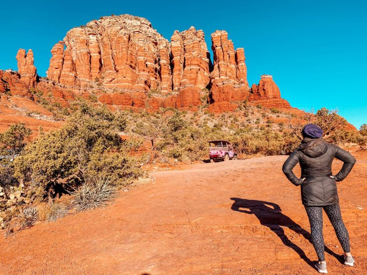 Woman with back to the camera with hands on her hips looking at a pink jeep that is parked in the distance with red rock formations behind it.
