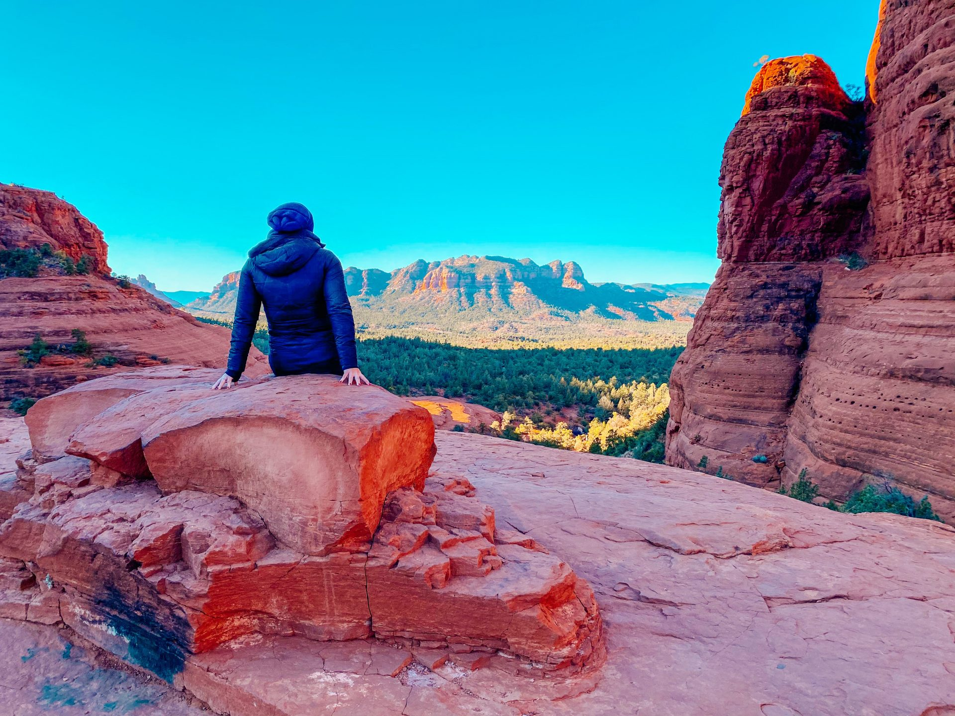 Woman sitting on a red rock formation with back to the camera looking out over Sedona Arizona to red rock formations in the distance. A cloudless blue sky is overhead.
