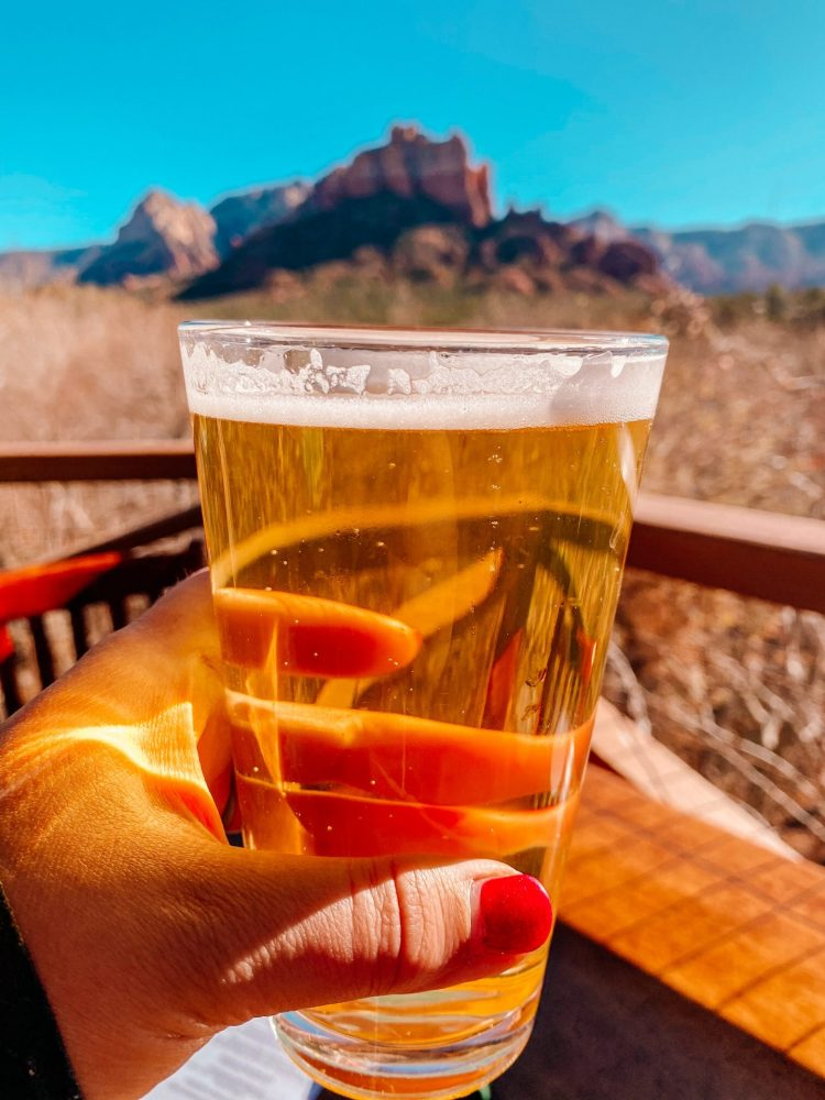 A glass of golden beer being held up with the red rocks of Sedona in the background from a patio