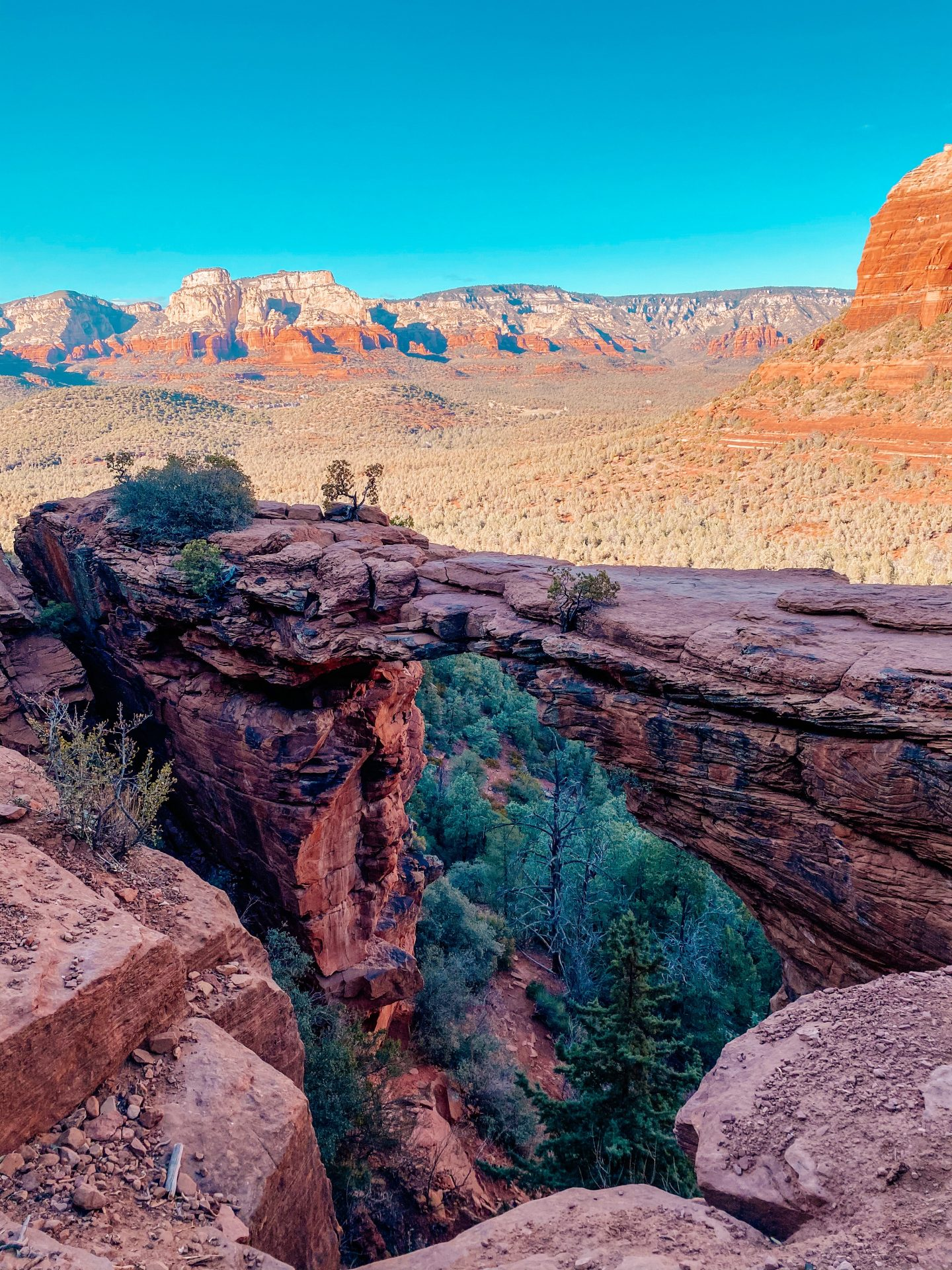 View out over Sedona, Arizona and red rock formations. A narrow bridge is shown close up and a blue cloudless sky.