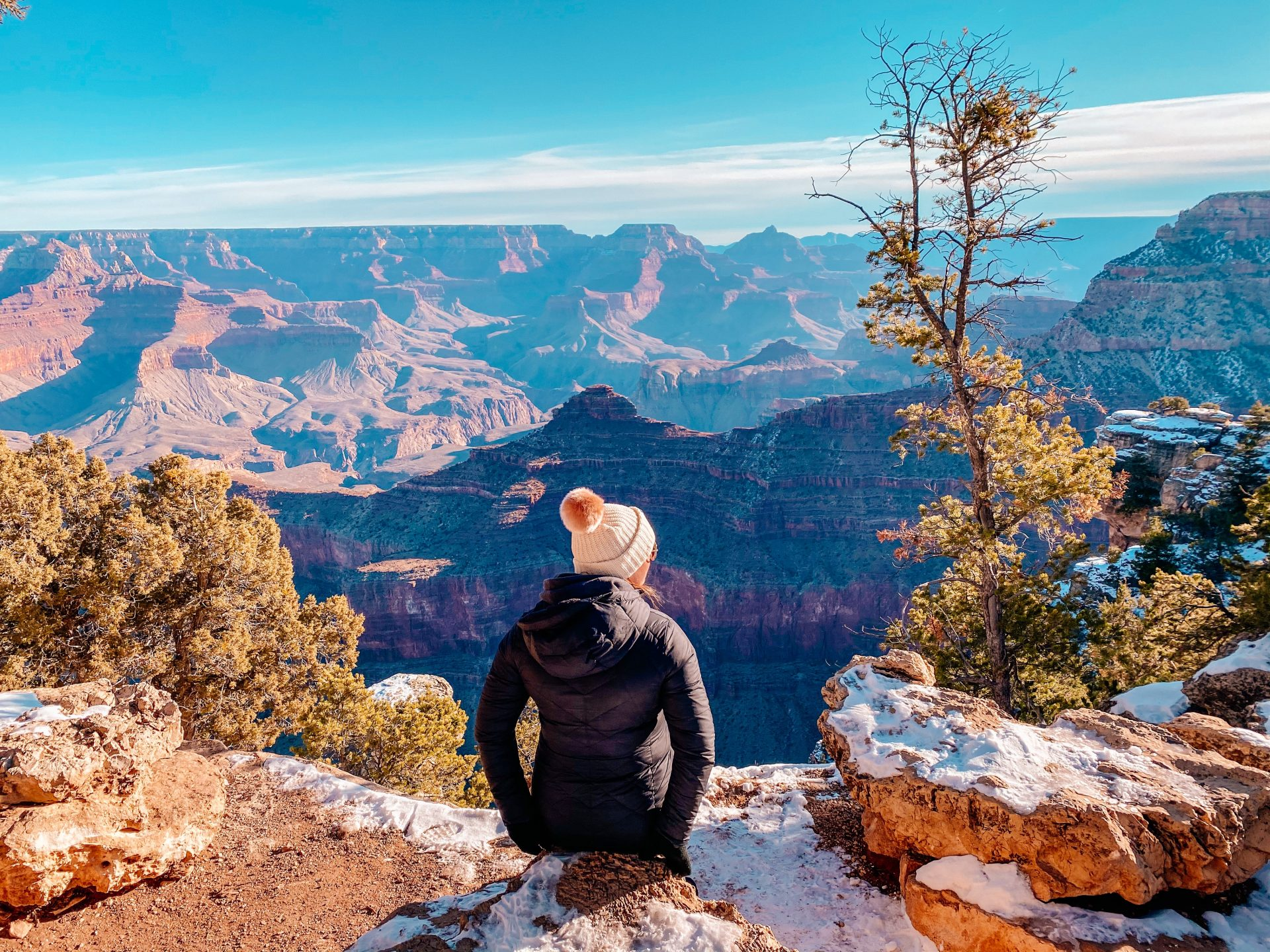 Girl with back to the camera wearing a black puffer jacket and natural colored winter hat sitting down gazing out into the Grand Canyon in Arizona.