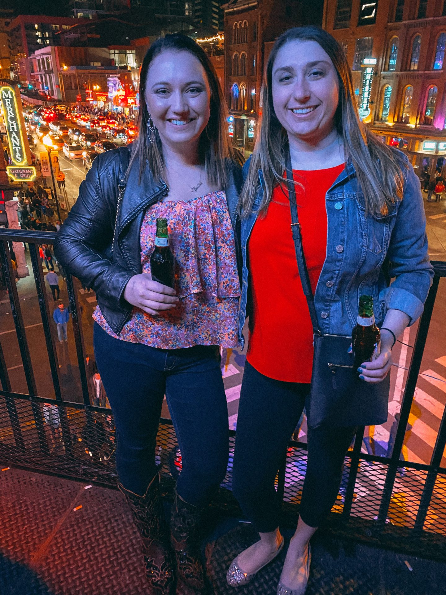 Two women showing the things to do in Nashville Tennessee standing on a balcony with Broadway in downtown Nashville's bright lights during night behind them. Wearing cowboy boots, jeans & a light jacket holding beers smiling.
