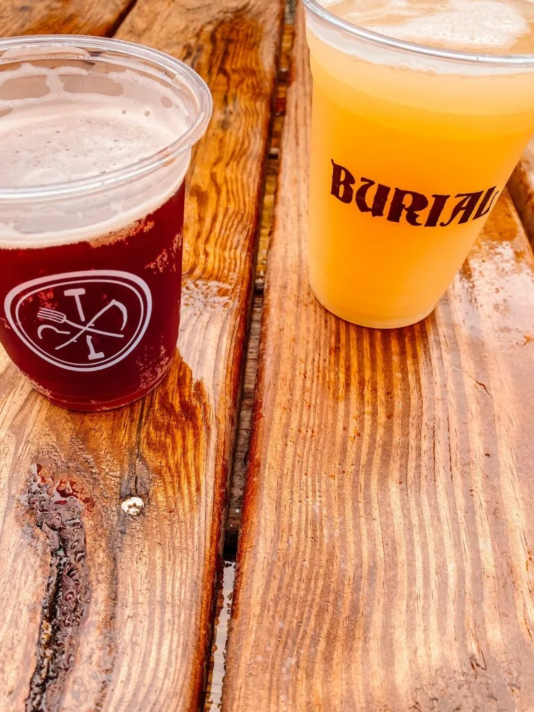 glasses of beer red and yellow in color with Burial logos on them sitting on top of a wooden table while spending a weekend in Asheville North Carolina
