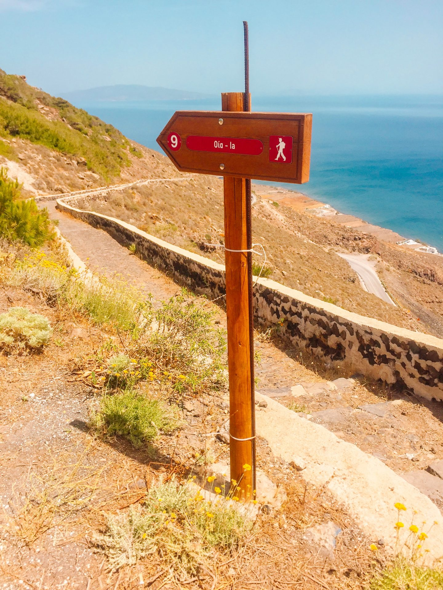 sign pointing to the path to hike from oia to fira on Santorini greece. Places to visit and things to do on Santorini.