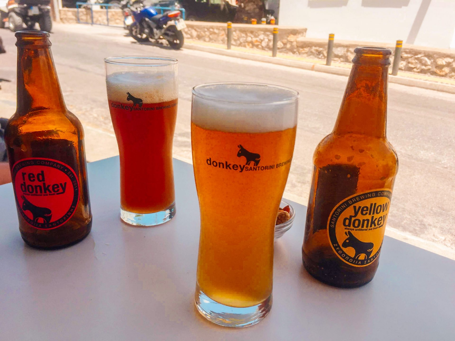 yellow donkey beers sitting on a table in Santorini Greece