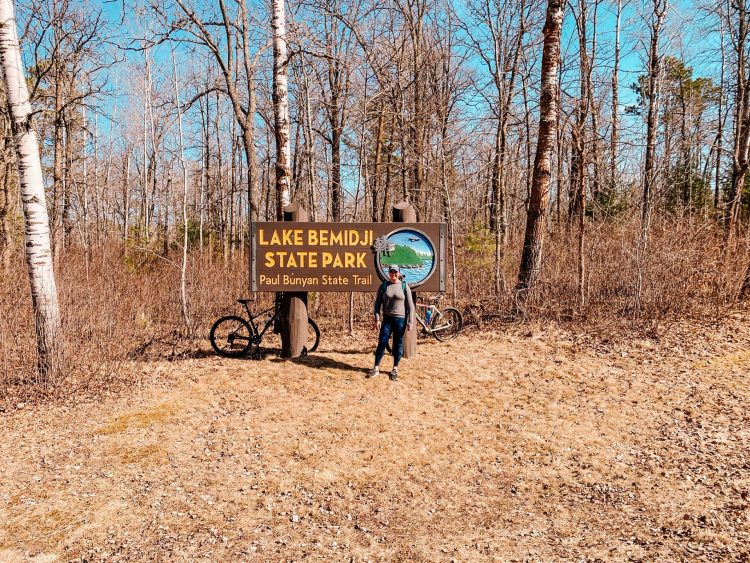 woman standing in front of the lake bemidji state park sign with bikes nearby