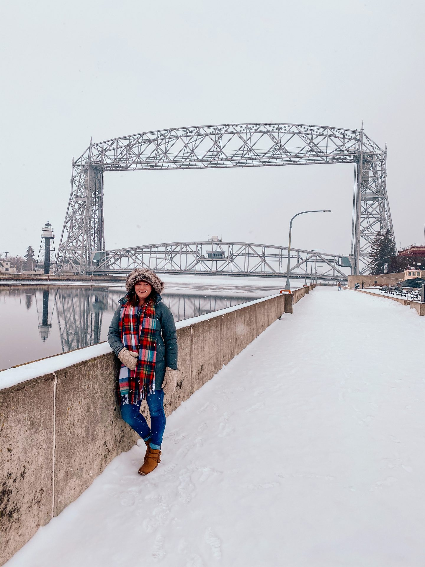 Woman in the winter standing in front of the aerial lift bridge in Duluth Minnesota on Lake Superior