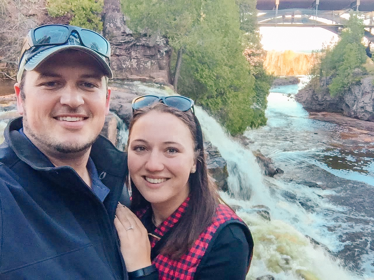 Woman and man standing near waterfall at Gooseberry Falls State Park in Minnesota