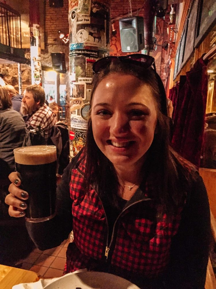 Girl wearing a buffalo plaid down vest with sunglasses on her head sitting in a bar smiling cheersing with a dark beer