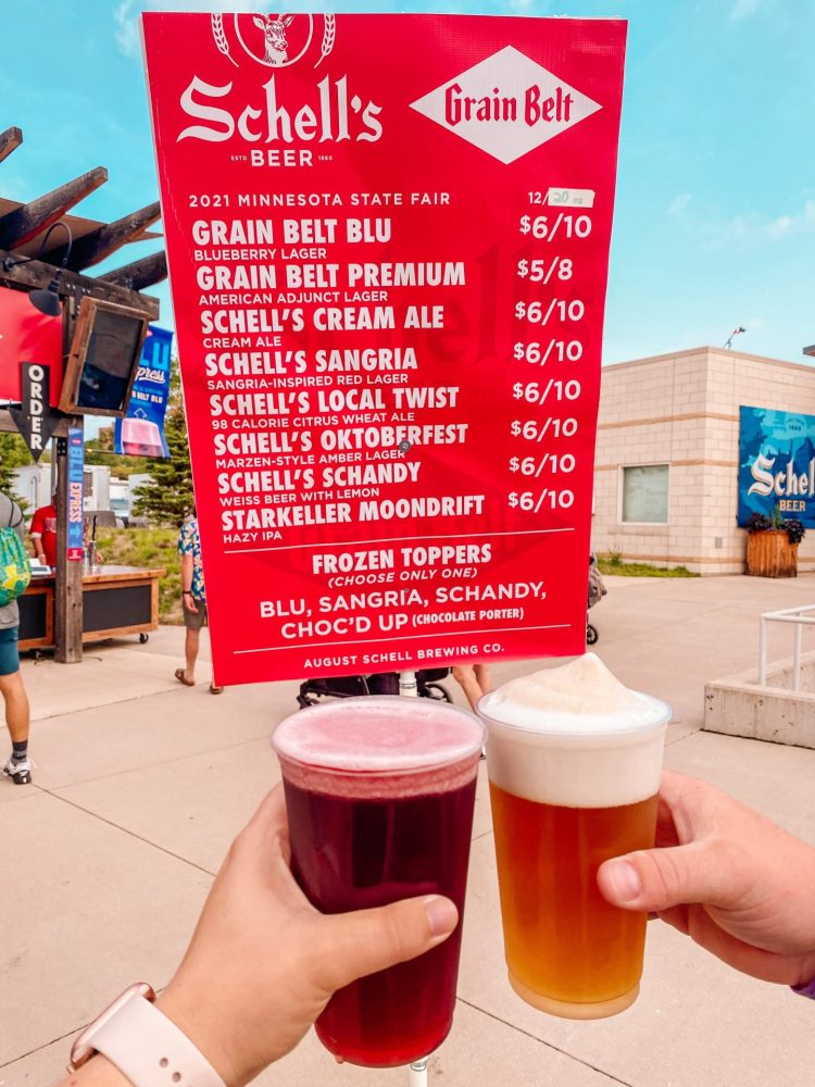 Cheers of two beers one blue blueberry beer with a cream ale with frozen beer slush tops under a sign showing all of the available beers at the minnesota state fair in 2021