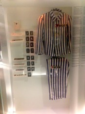 an original prisoner's uniform: In addition to a number patch, each prisoner received a colored triangle patch, signifying which class of prisoner he was: a red patch meant a political prisoner; a pink match meant a homosexual prisoner, etc