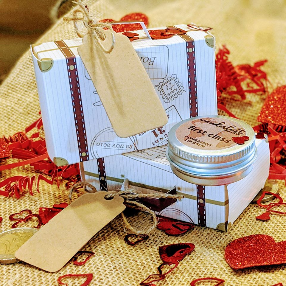 Two small gift boxes that look like vintage suitcases stacked up on top of a burlap sack. Red heart confetti sprinkled around. Peppermint Wanderlust Skincare lip balm on top of the box.