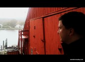 The bold red barn stands out against my brother's distant gaze at the Mystic Seaport.