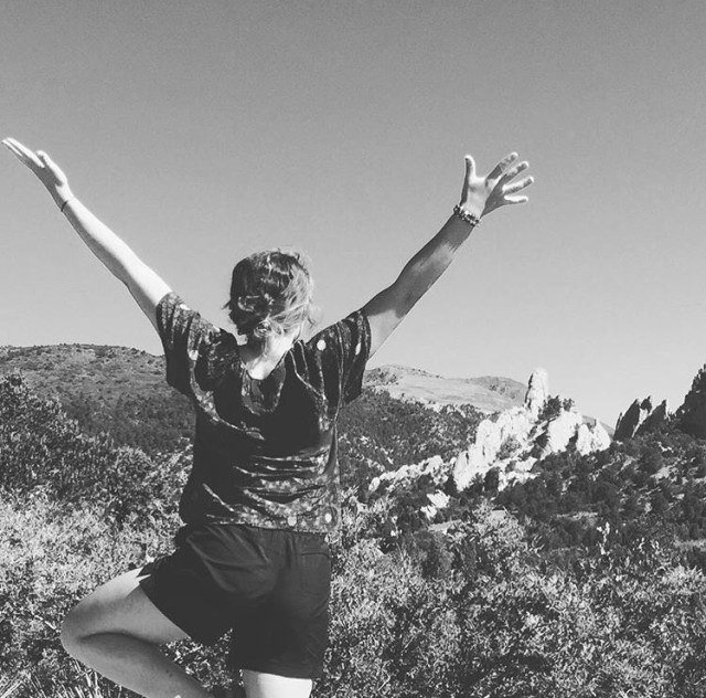 black and white photo, woman facing mountains in Colorado with arms spread open above