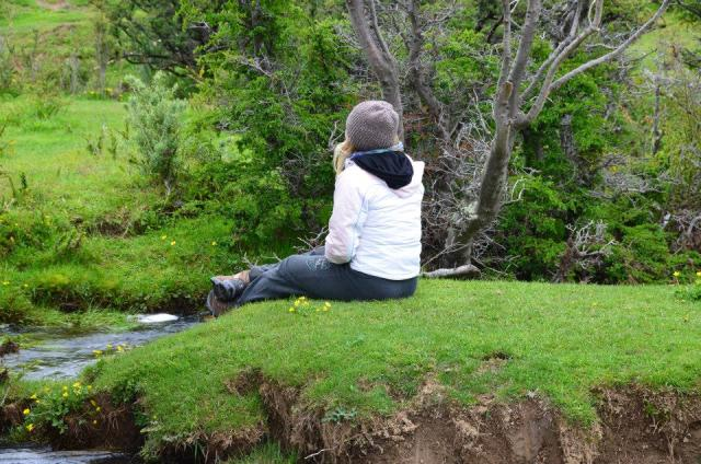 a girl surrounded by green, sitting and thinking in Patagonia