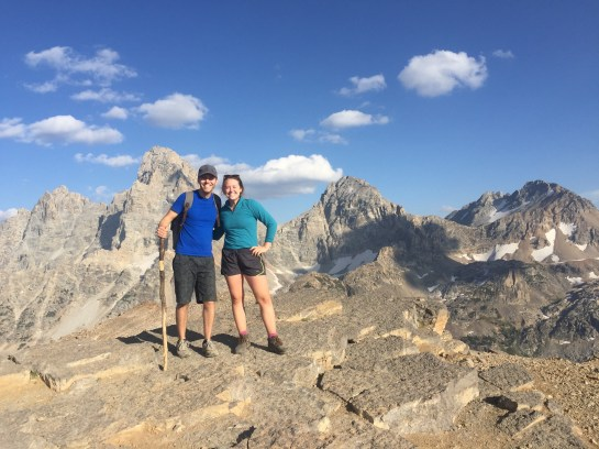 Two people standing at the top of a mountain with clouds and the grand Tetons behind them.