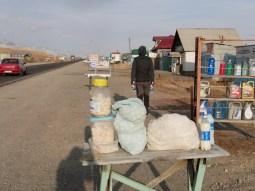 Village on the way. Selling the traditional kyrgyz snack: Kurut. Little dried balls made of milk.// Hier wird der traditionelle kirgisische snack verkauft: Kurut: Harte Bällchen aus getrockneter Kuhmilch.