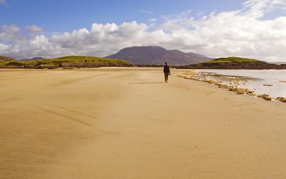 My friend walking down a desolate beach in County Mayo, Ireland
