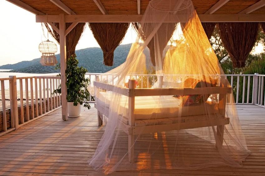 Bed on deck of Karia Bel' Hotel room at sunset