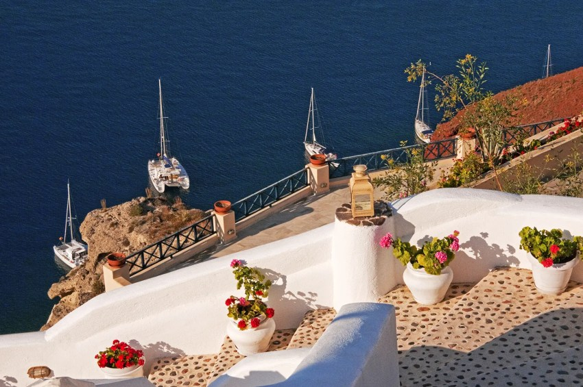Stairway with plants and sailboats anchored off the coast, Oia, Santorini, Greece