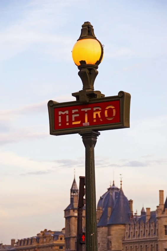 Metro sign on lampost at sunset, Paris, France