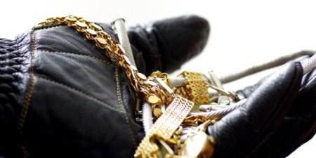 Einbrecher hält Diebesgut in Hand mit Lederhandschuh