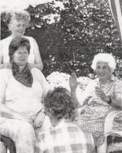 Picture of Dottie Hook giving herbalist Jenny Boys a massage in the garden of Ailsa Lawrence.