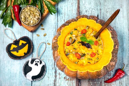 Soup with lentil in the carved pumpkin, ghost and laughing black lantern toys on the blue wooden background at Halloween party