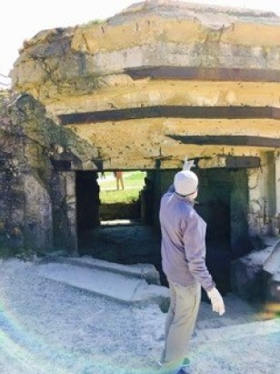 Brother-in-law Cary Johnson pointing to war damage on gun casement at top of Pointe du Hoc, Normandy.