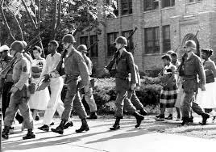 Troops from the 101st Airborne protect nine Black students walking to class at Little Rock, Arkansas' Central High School.