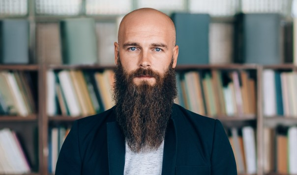 Portrait of bearded hipster man in library