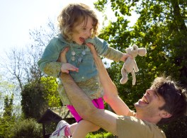 Young girl being held in the air by her father in The Rookery, Streatham Common photographed by Anna Hindocha/Warm Glow Photo