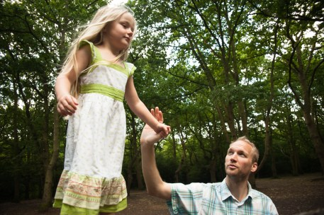 Young girl balancing on a tree with her father in Streatham Common Woods, photographed by Anna Hindocha/Warm Glow Photo