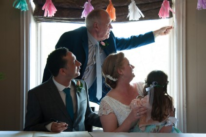 Bride, Groom, daughter and father of the bride during signing of the register at The Rosendale, Dulwich. Photographed by Anna Hindocha/Warm Glow Photo.