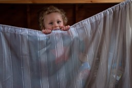 Young boy hiding behind curtain. Photographed at home by Anna Hindocha/Warm Glow Photo