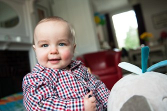 One year old boy on a ride on toy in his living room. Photographed by Anna Hindocha/Warm Glow Phot