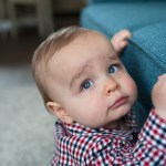 One year old boy holding on to sofa in his living room. Photographed by Anna Hindocha/Warm Glow Photo