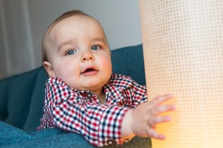 One year old boy playing with light in his living room. Photographed by Anna Hindocha/Warm Glow Photo