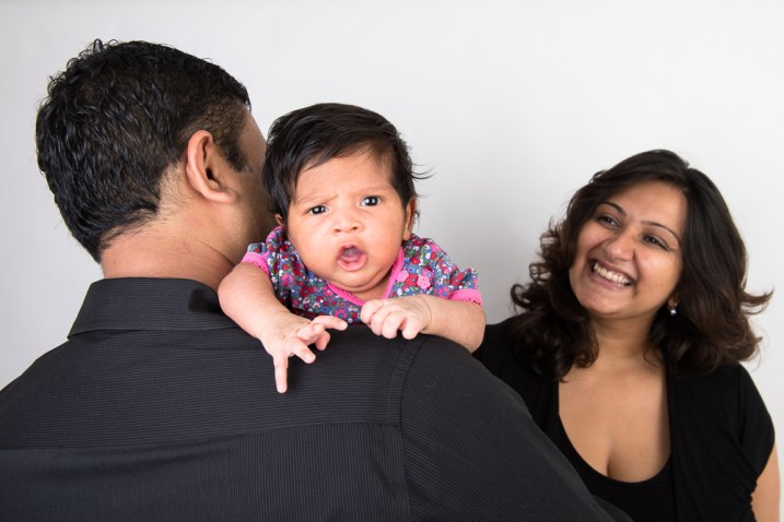 Studio photo of a newborn baby girl and her parents. Photographed by Anna Hindocha/Warm Glow Photo