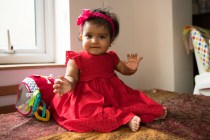 7 month old baby girl in red dress sitting on table, lit by window.